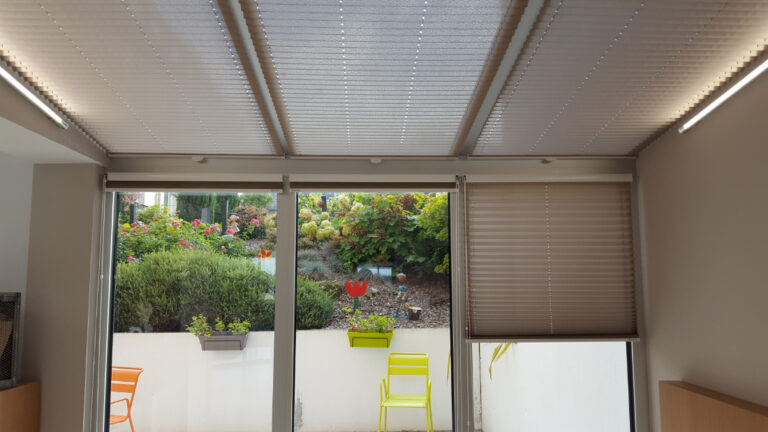 Stores plissés sur des portes fenêtres et des vitres au plafond