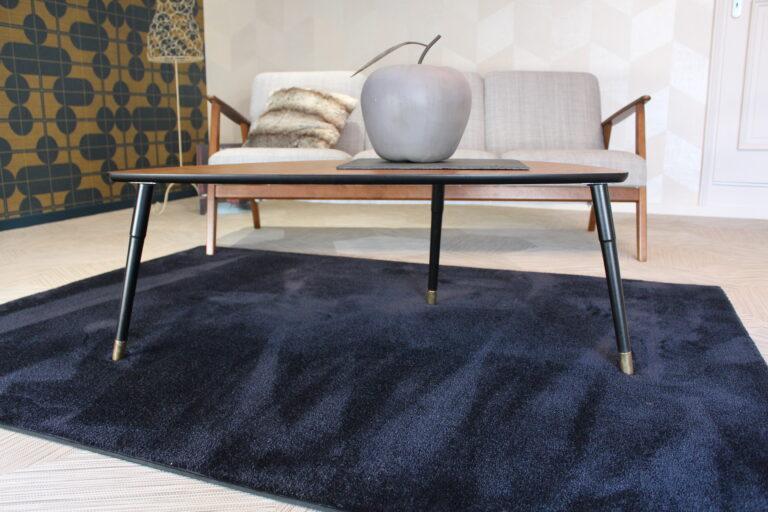 Pièce avec une table sur un tapis et un canapé