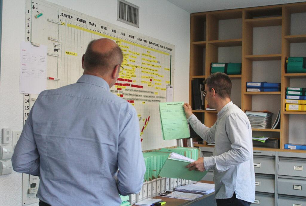Conducteurs de travaux devant un panneau d'organisation