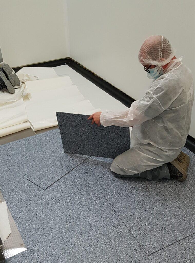 Compagnon en tenue qui pose un sol en PVC dans une salle blanche